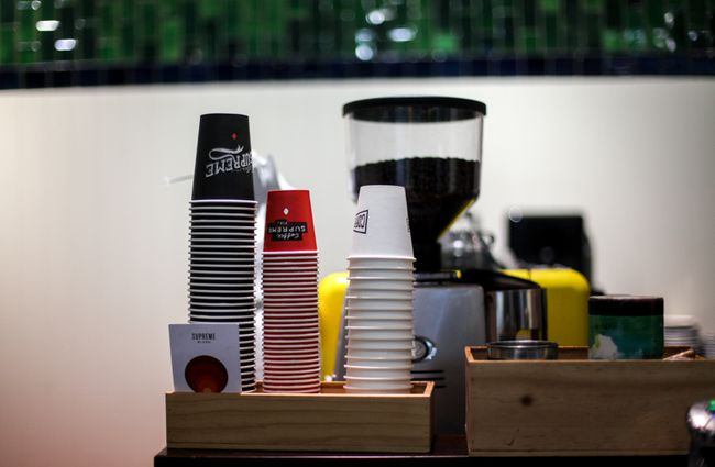 Coloured coffee cups on top of coffee machine.