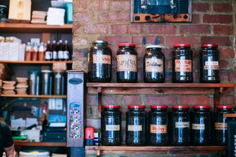 Jars of coffee on a wooden shelf against a brick wall.