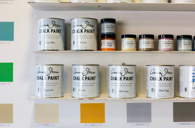 Tins of chalk paint on a shelf.