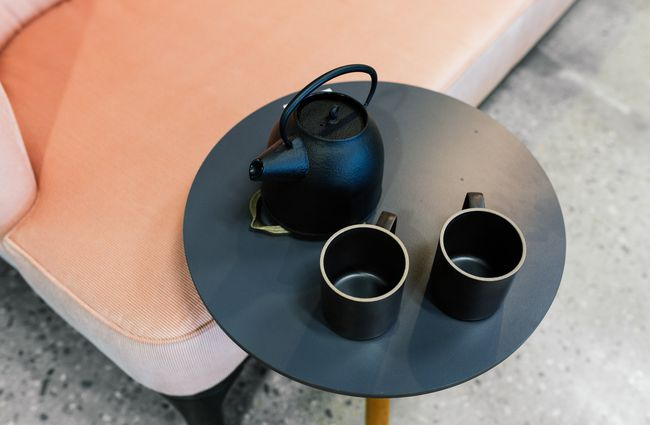 Tea pot and cups on a small table.