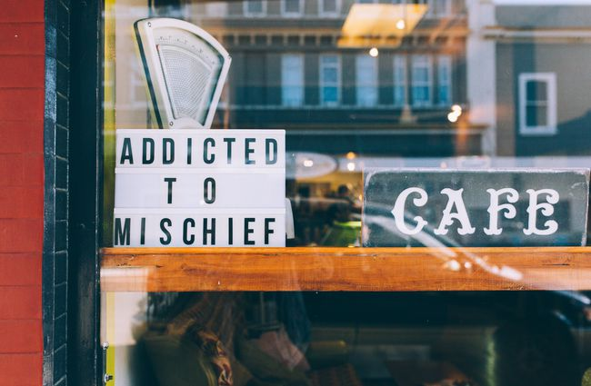 Addicted to mischief sign in window of cafe.