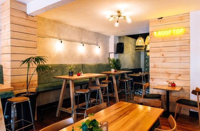 Large restaurant space downstairs with wooden walls and colourful seating.