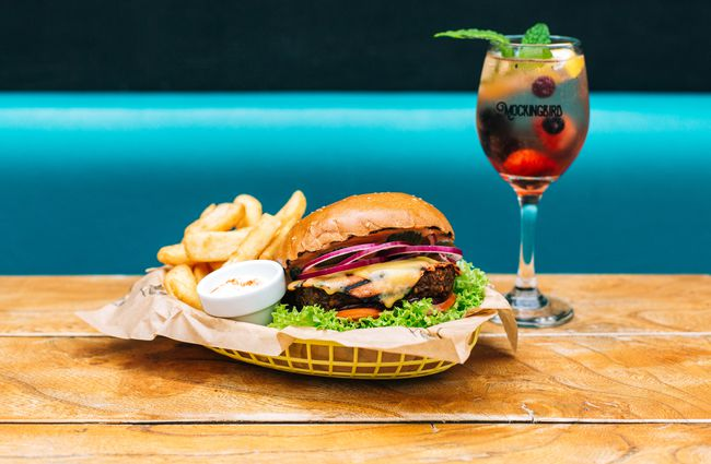 Burgers and fries on a table with a glass of Sangria.