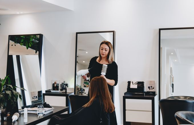 A woman blow drying hair inside Mod's Merivale hairdresser in Christchurch.
