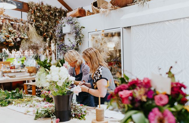 Two women create bouquets behind a big workbench.