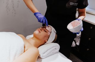 Produce being applied to a face during a facial.