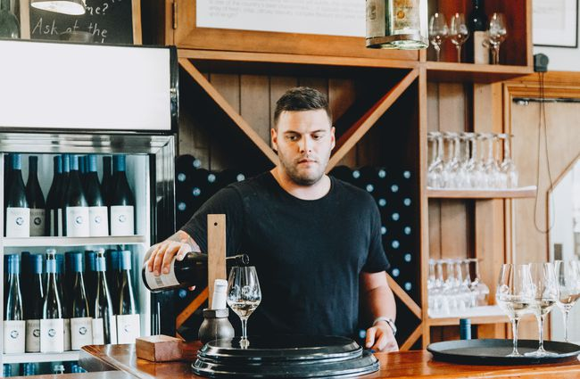 A man pouring wine behind the counter at Pegasus Bay winery and restaurant in North Canterbury.