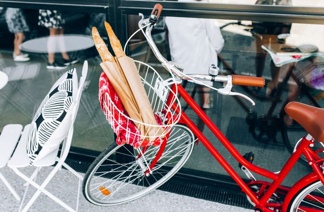 Red bike with basket of baguette.