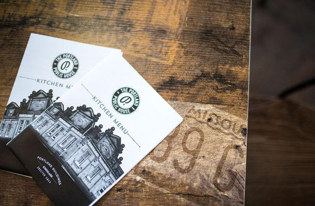 Portland Public House menus against a wooden table.