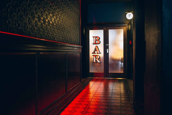 Bar sign in a dark hallway.