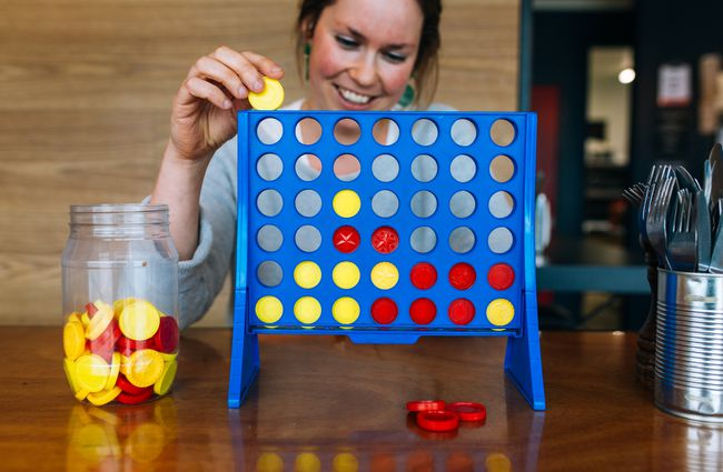 A woman playing Connect Four at a table.