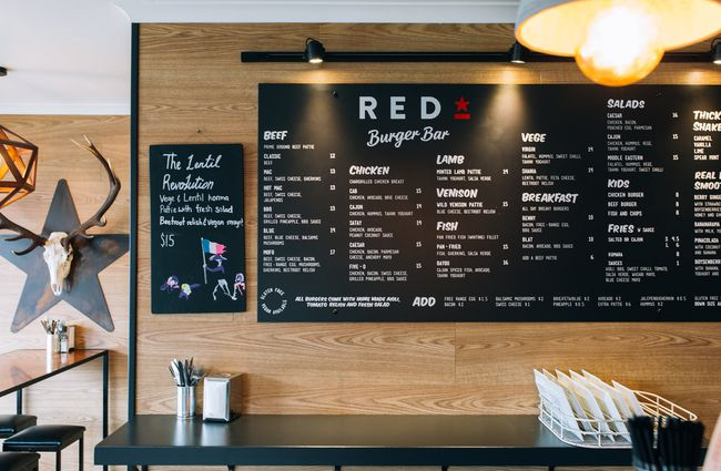 A large menu board on a wall.