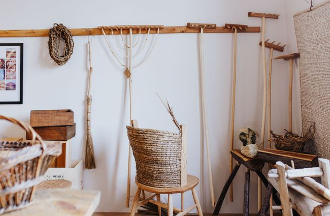Rakes and items made of wood hanging on a white wall.
