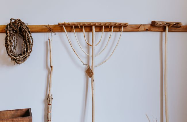 Wooden rakes hanging on a wall.