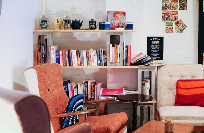 Books on bookshelves behind vintage seating.