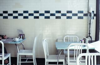 White tables and chairs by tiled wall.