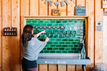 A woman pouring a beer from a tap.