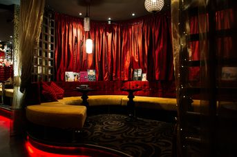The seating area in the bar surrounded by red velvet curtains.