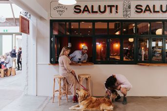 Woman drinks wine with her dog outside a tapas bar.