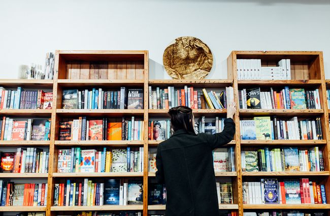 A woman reaching for books on a shelf.