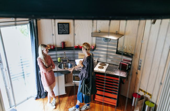 Two women chatting inside a kitchen.