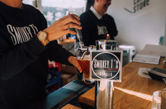 Bartender pours a beer at Smoky T's, Christchurch.