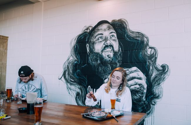 Customers eating in front of mural at Smoky T's, Christchurch.