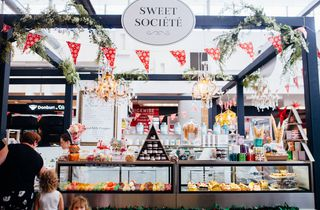 Serving counter with sweet treats and hanging signs.