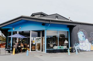 Outside view of bright blue Switch cafe with umbrellas.