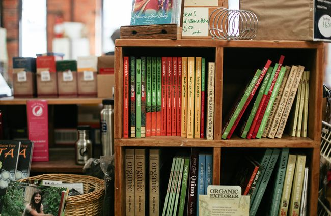 Gardening books on wooden shelf.