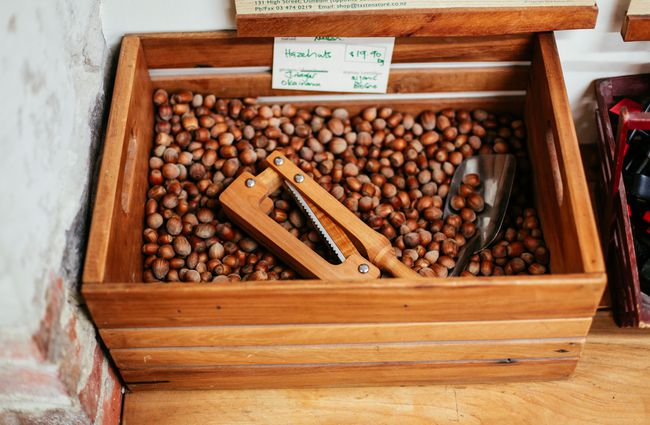 Wooden box full of hazelnuts with self serve scoop.