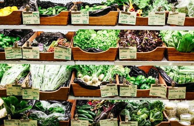 A full shelf of green vegetables in wooden boxes.