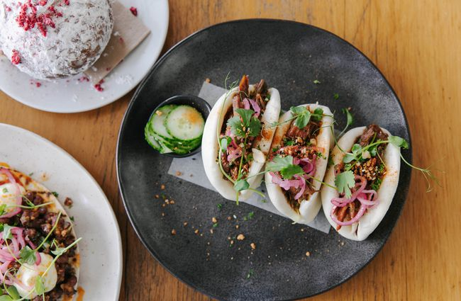 Three bao buns on a plate.