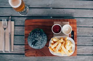 A flat lay of a burger, fries and a beer.