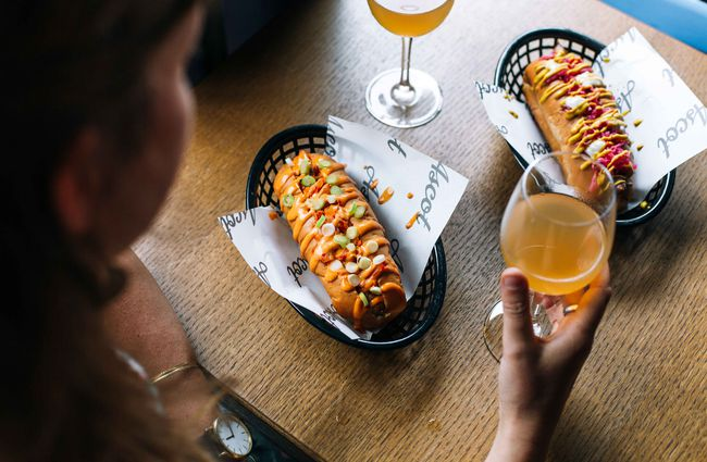 Hotdogs and wine on a table.