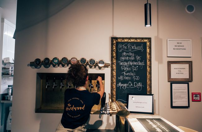 Waitress pours a beer at The Birdwood, Christchurch.