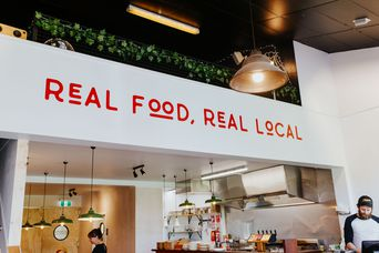 Real food real local signage above counter.