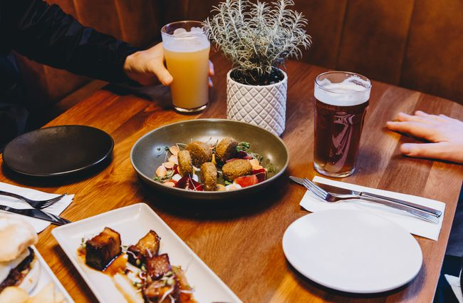 Plates of food and pints of beer on a table at The Craft Embassy bar Christchurch.