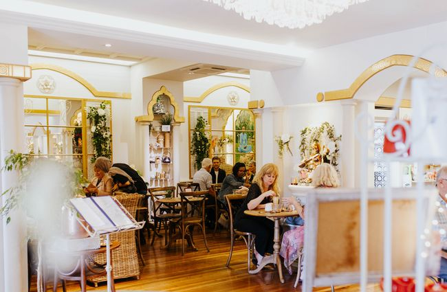 White and gold cafe interior with arches.
