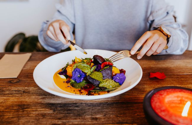 Person eating a plate of colourful food.