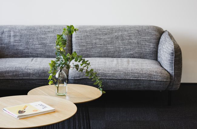 Grey couch with low wooden table in front.