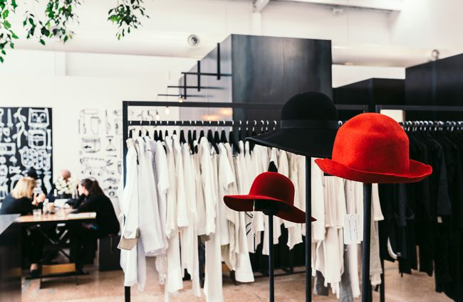 Red hats by clothing racks.