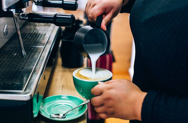 Barista pouring coffee into green cup.
