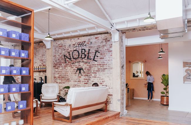 Brick wall and signwriting with armchairs underneath.
