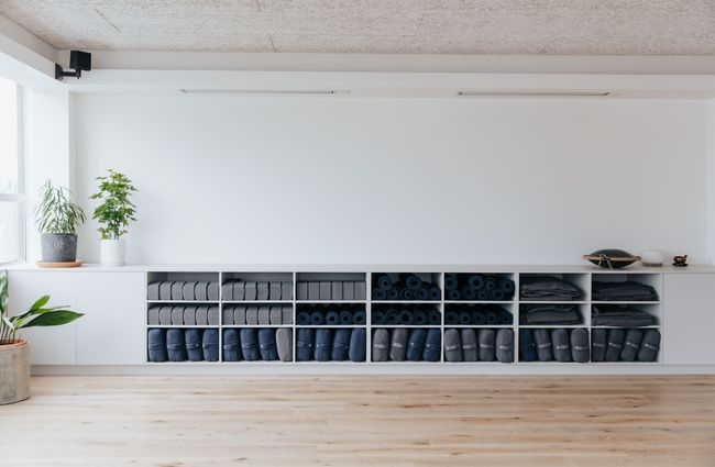 Wall of open shelves with rolled yoga mats.