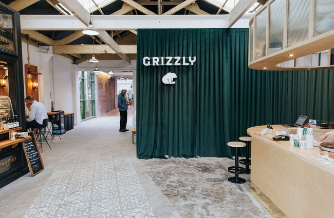 Green curtain with a Grizzly Baked Goods bear on it.