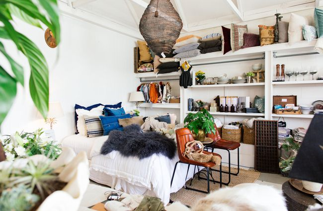 A large bed, linen and homewares on shelves.