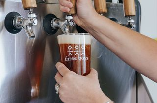 Woman pulling a pint using large wooden handles.