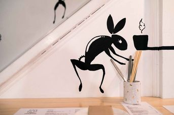 Black rabbit on a white wall.