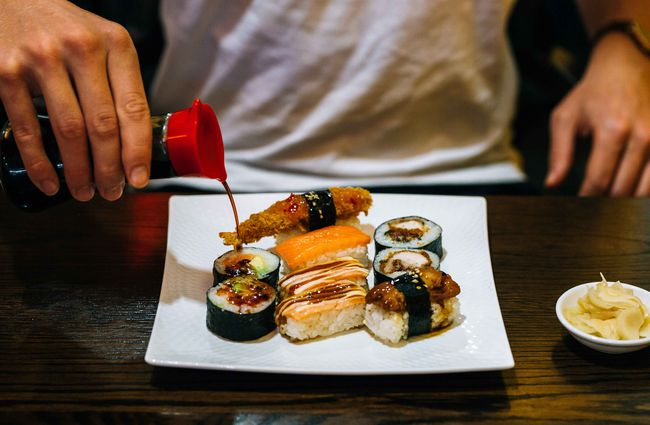 Man pouring soy sauce on a plate of sushi.